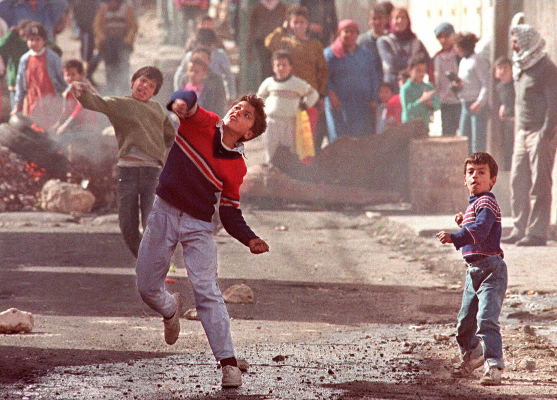 (FILES) - Picture dated 01 February 1988 of children throwing stones to soldiers in the Am'ari refugee camp near Ramallah, to protest against Israeli occupation. A decade after, 08 December, the Intifada generation is still disillusioned with a peace process which they hoped would complete their struggle for a state.        (Photo credit should read ERIC FEFERBERG/AFP/Getty Images)