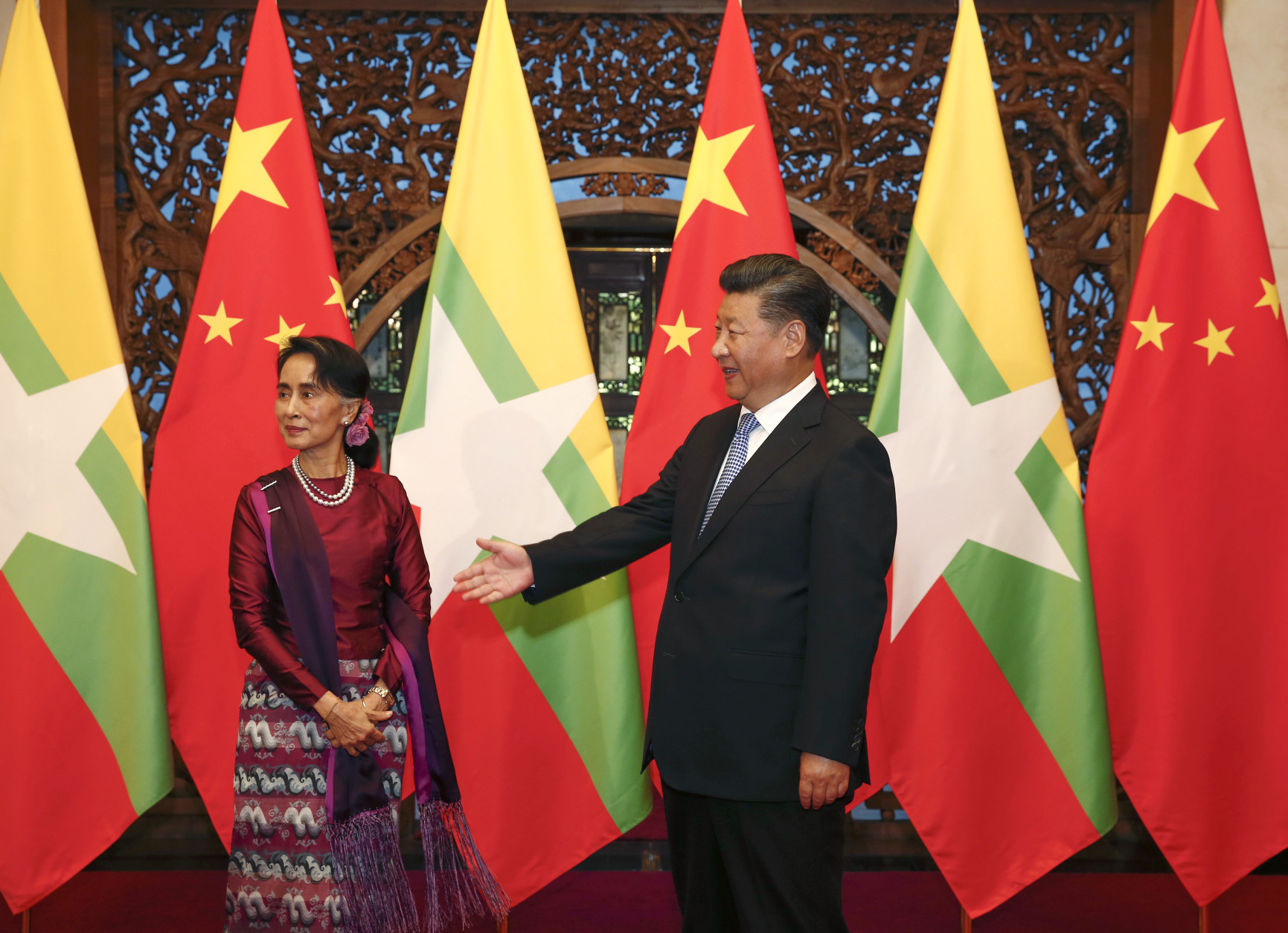 Myanmar's State Counselor Aung San Suu Kyi, left, and Chinese President Xi Jinping, right,  wait for Myanmar delegates to enter for a meeting at the Diaoyutai State Guesthouse in Beijing, China, Friday, Aug. 19, 2016.  Suu Kyi was welcomed by Premier Li Keqiang at a formal ceremony Thursday at part of a visit that will include talks with President Xi. The trip ending Sunday is her first to China since her party won a historic majority last year.(Rolex Dela Pena/Pool Photo via AP)